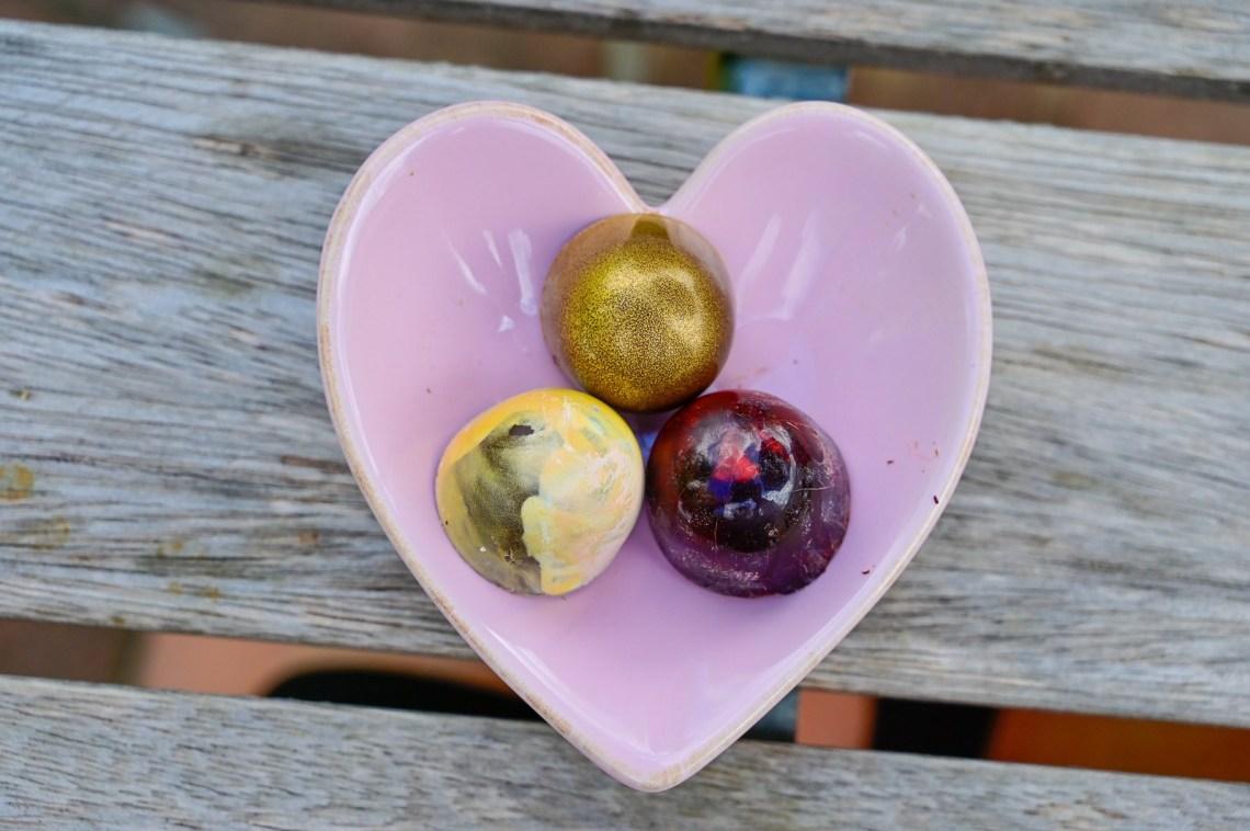 Three pralines on a heart-shaped dish