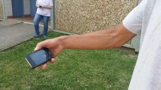 Un voisin regarde l'arrestation de la femme du suspect sur son portable ©Rue89Lyon LB