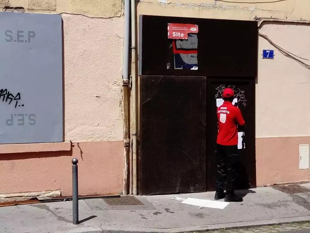Après l'intervention de la police, l'entrée du squat est gardée par un agent de sécurité.