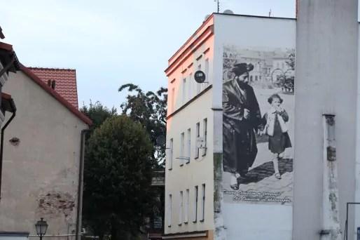 Sur les façades des maisons du centre d'Oswiecim, des photos rappellent la vie paisible avant la Shoah. Plus de la moitié de la population était alors de confession juive. Aujourd'hui il n'y a plus aucun juif dans la ville.