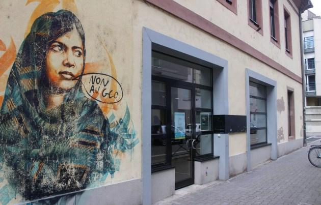 Les lettres de l'ancienne mairie de quartier sous le regard d'une fresque de Dan 23 représentant Malala (auquel un autre tag s'est ajouté) (photo JFG / Rue89 Strasbourg)