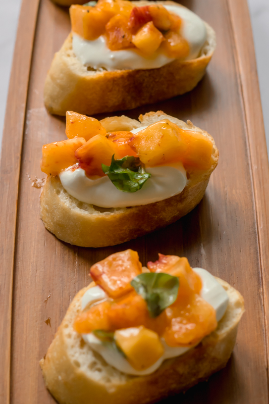 peaches and goat cheese with basil on a crostini