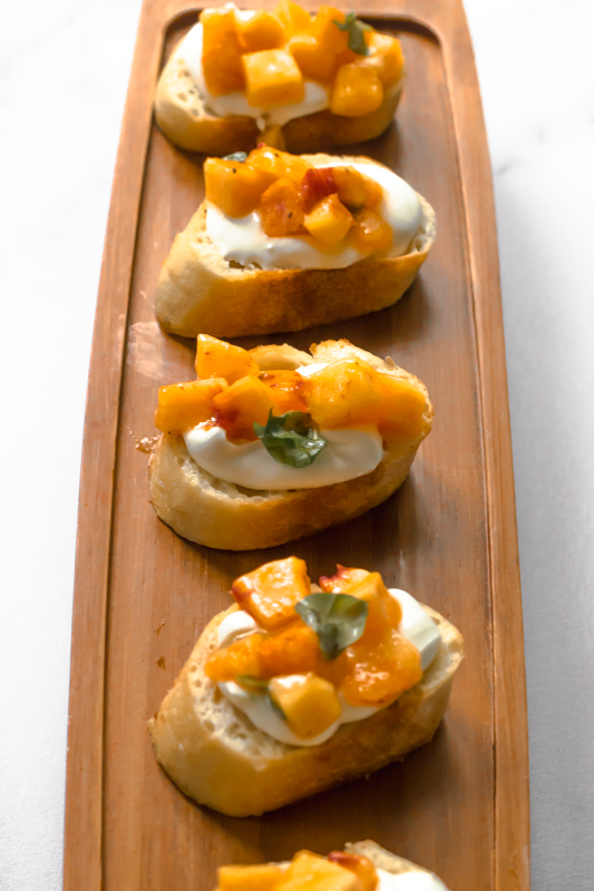 narrow tray of peach and goat cheese bruschetta appetizer