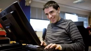 Man Smiling while using a computer.