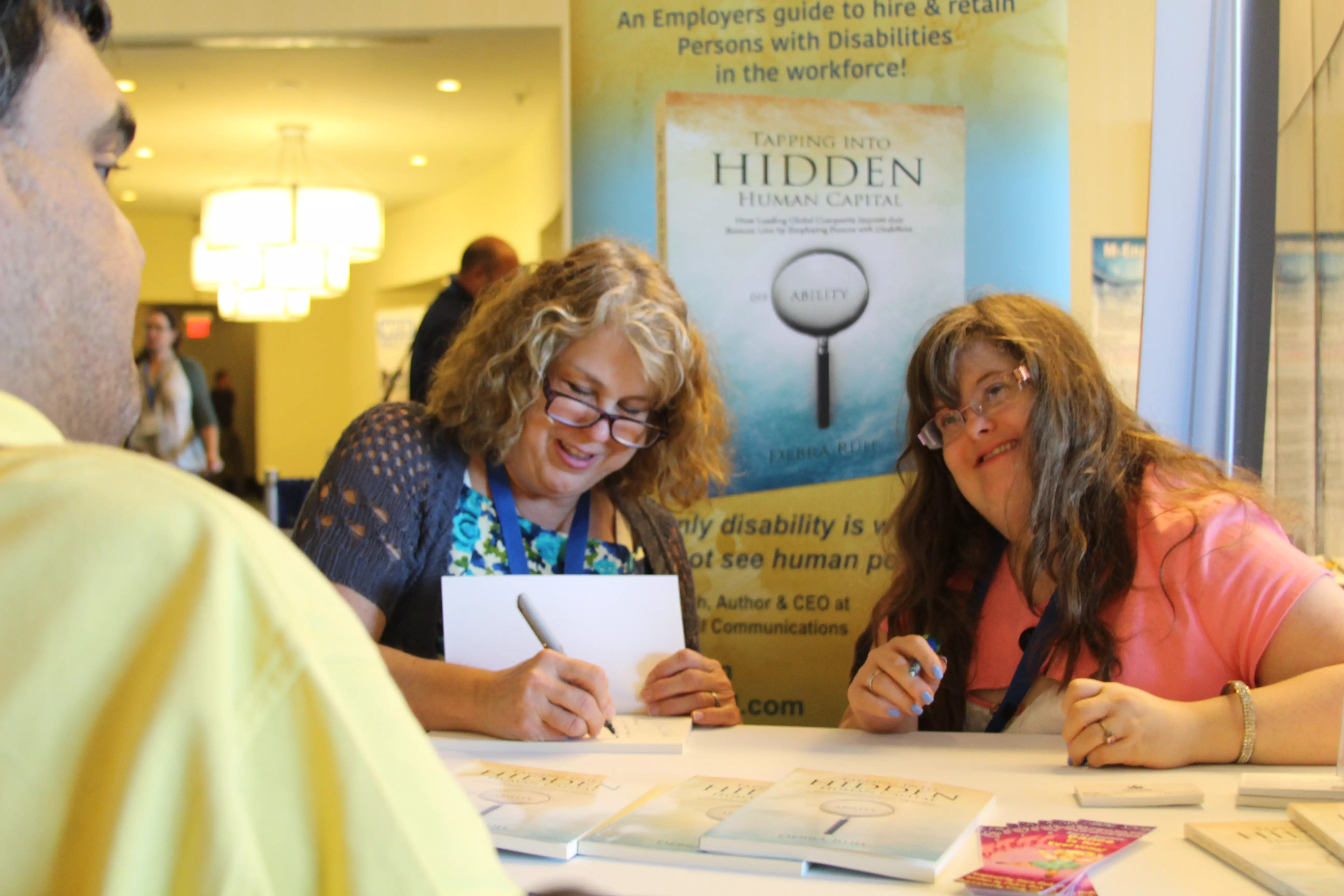 Debra Ruh (L) and daughter, Sara (R) are all smiles while Debra signs her book for a fan — published by G3ict.