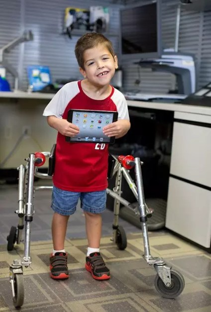 Young boy holding an iPad at an Assistive Tech Demo, Taken by Raminta Zebrauskas - AMAC Team Photographer