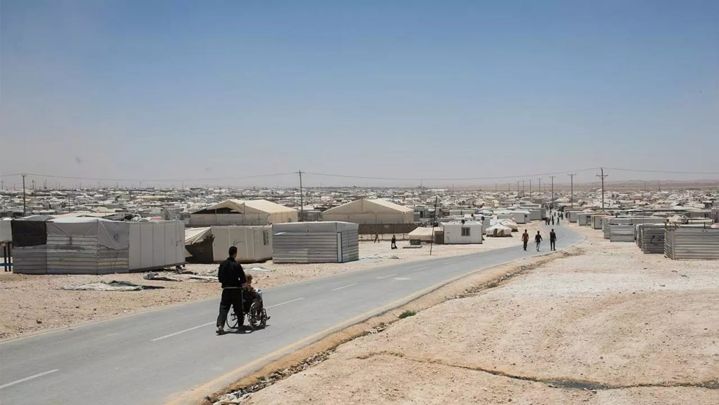 Person with disabilities on a street in a huge refugee camp.