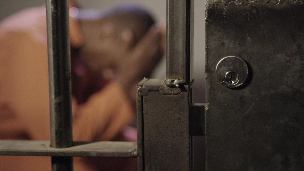African man in jail out of focus behind bars of his prison cell