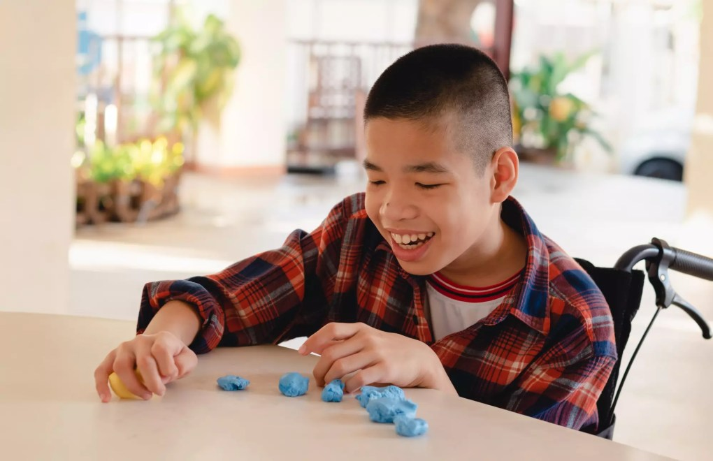 Asian disabled child on wheelchair molding clay