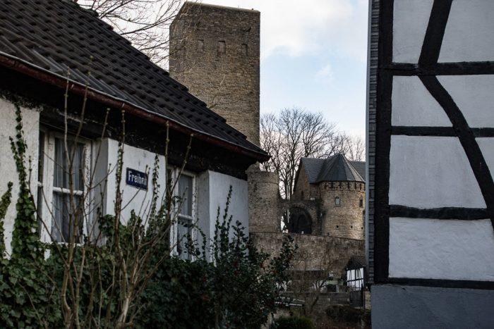 Zahlreiche Fachwerkhäuser rahmen die Burgruine ein.