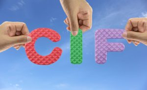 Hand arrange alphabet CIF of acronym Cost Insurance and Freight in Goods transport port ship.