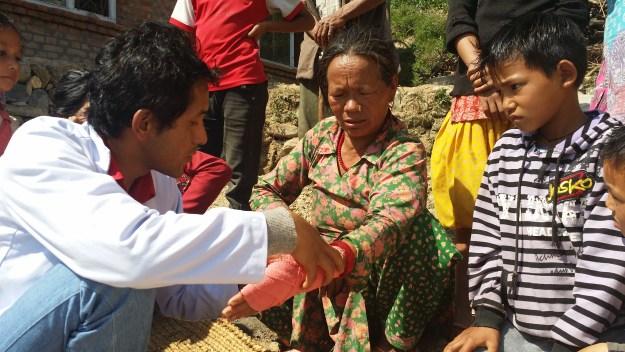 Medical Person helping an earthquake survivor at Simpani Village