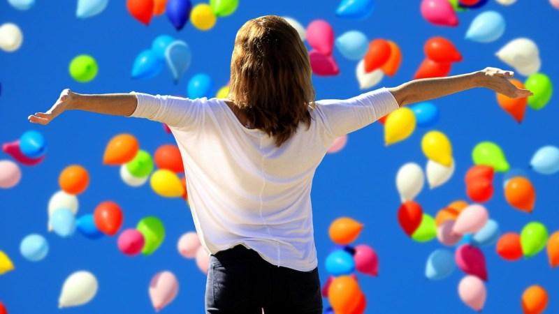 vergroot je zelfvertrouwen. Een vrouw staat met haar rug naar de camera en kijkt blij naar een blauwe lucht met ballonnen