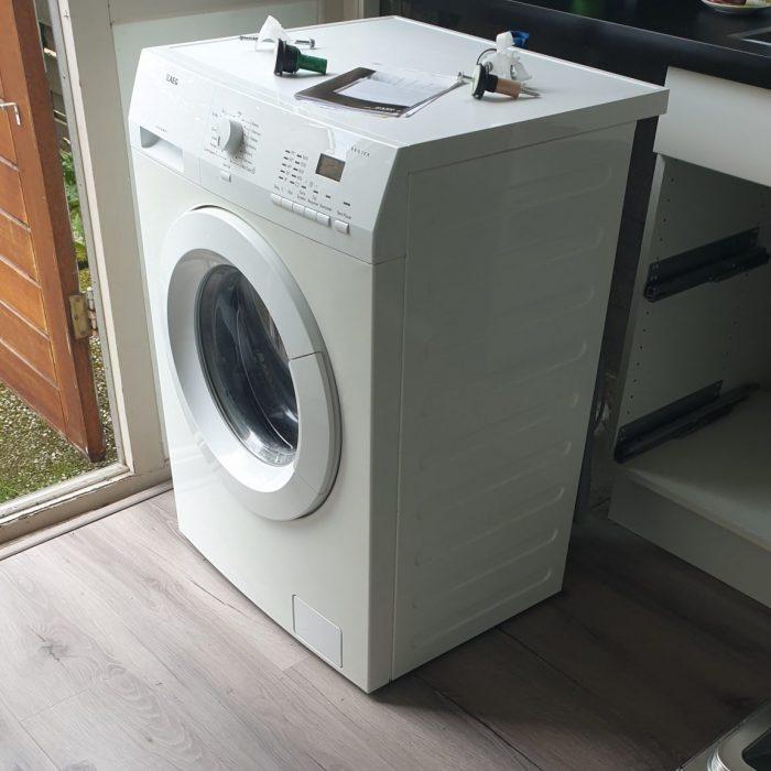 De oude wasmachine staat klaar om opgehaald te worden
