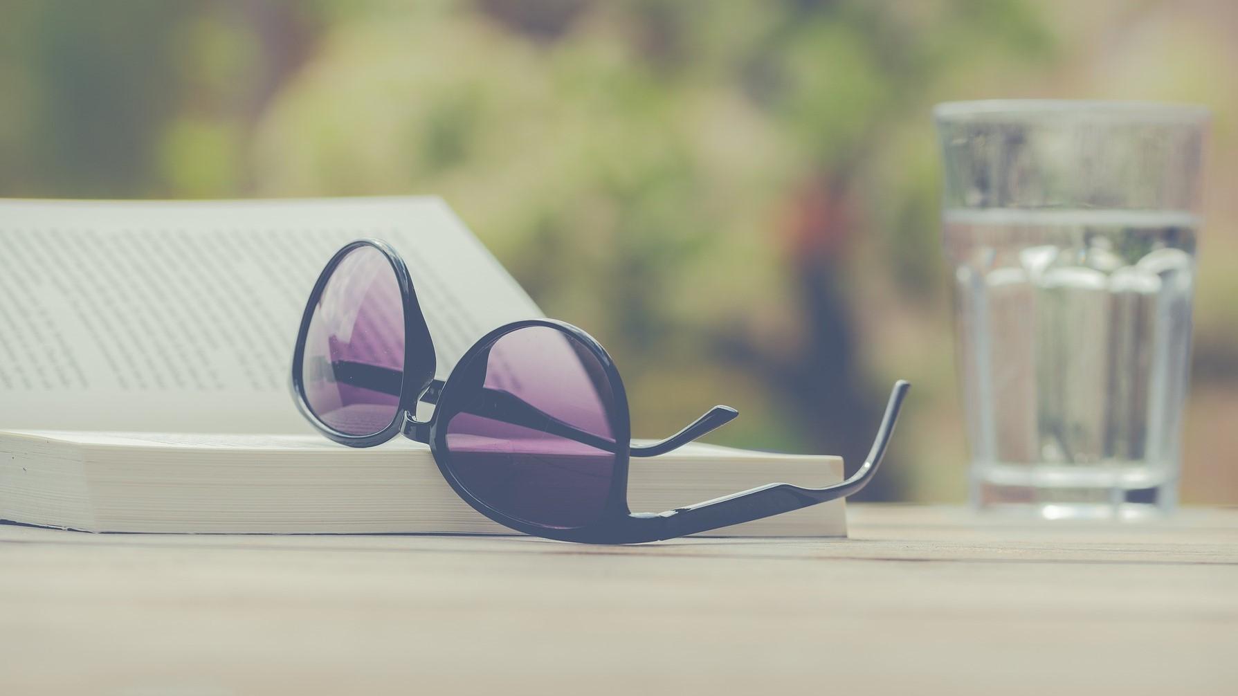 Kleine dingen in het leven. Een boek, zonnebril en glas water op tafel