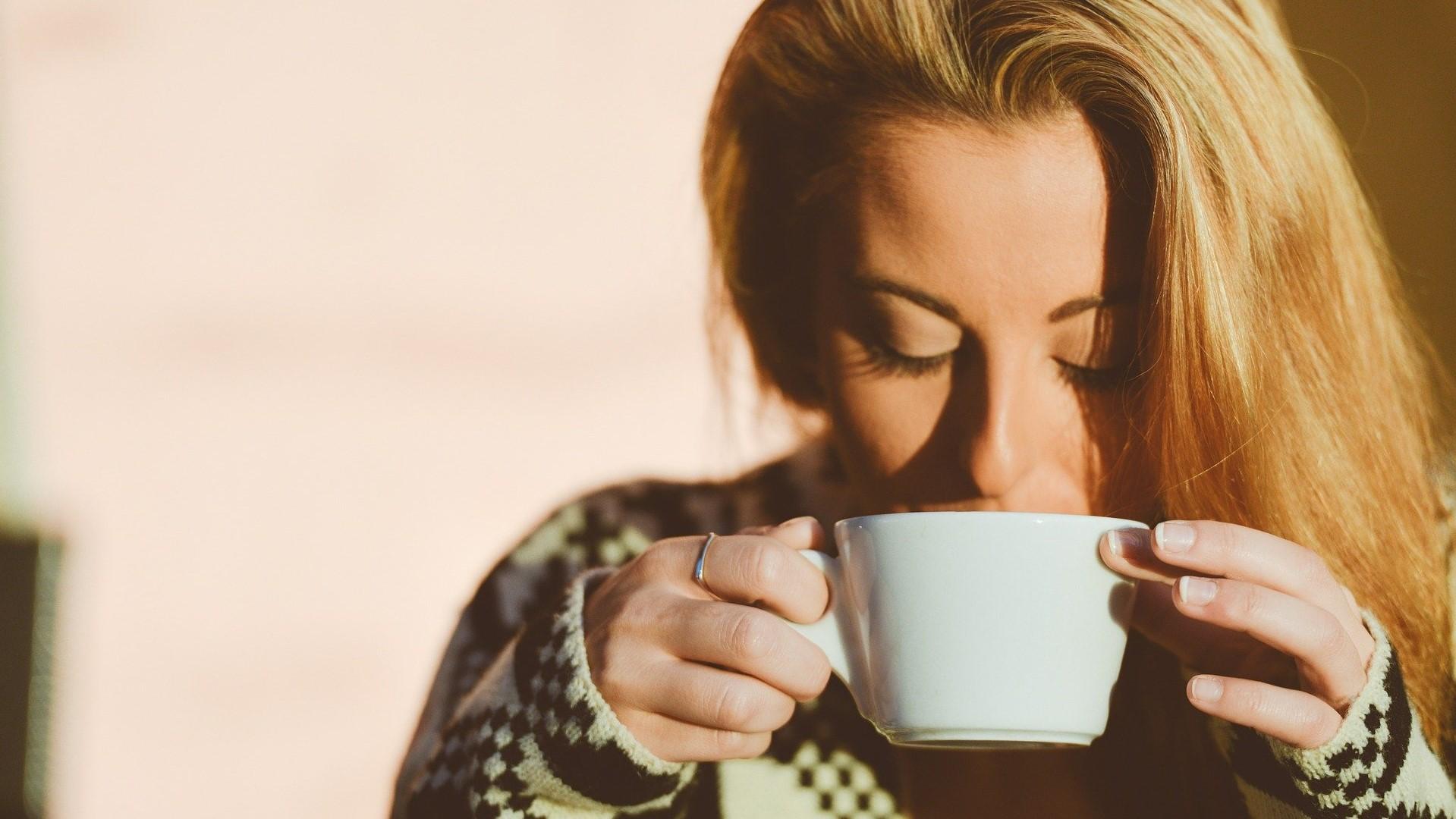 Een vrouw die wakker wordt na het slapen met een kopje koffie.