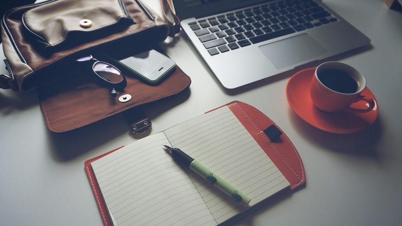 Zaken als een rugzak, laptop, telefoon, bril, notitieboekje met vulpen en een kopje koffie.