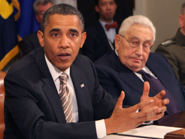 President Barack Obama and Henry Kissinger sitting at a table