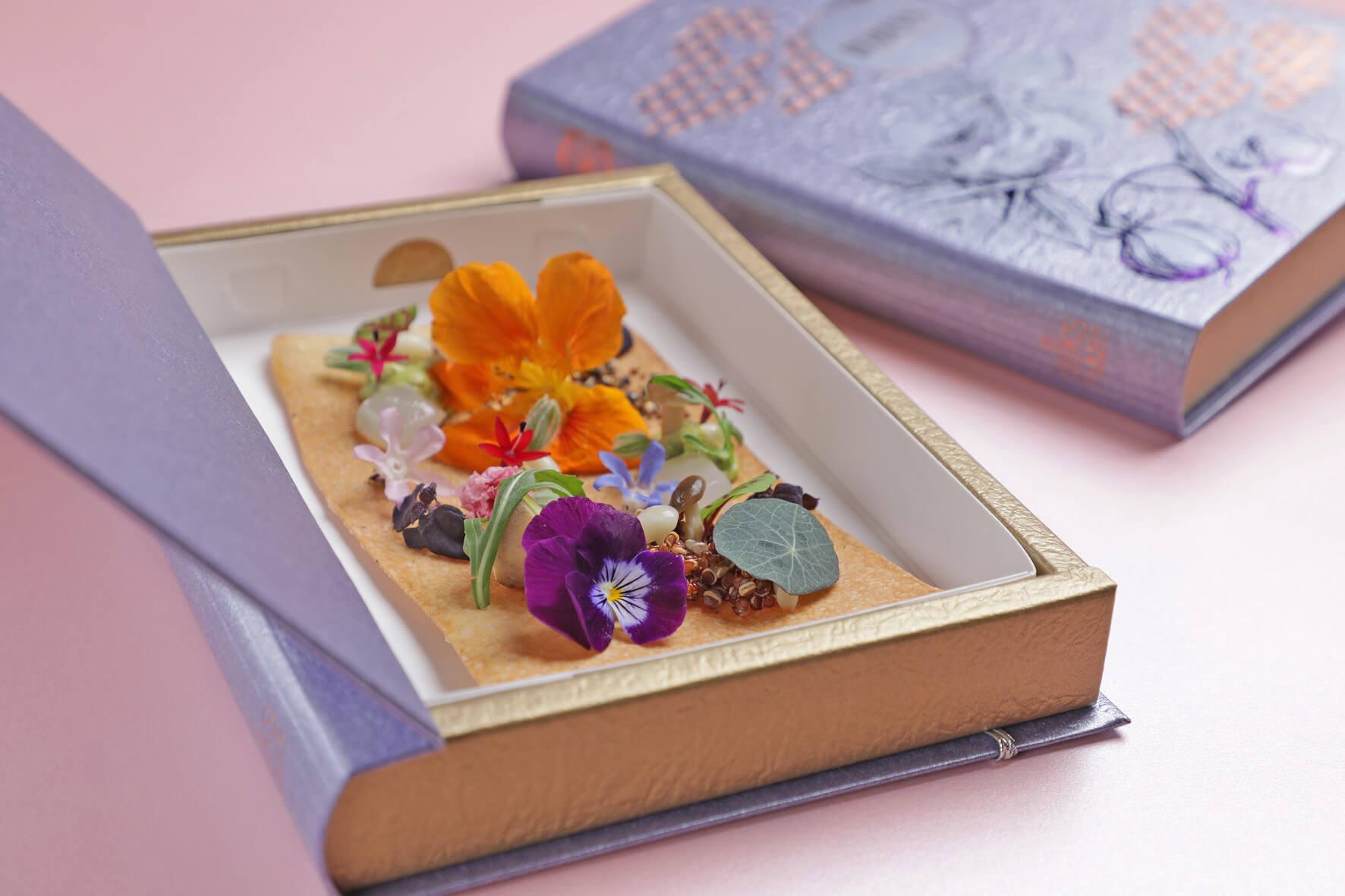 開胃菜「初春」以精美的書本盛裝曼波魚膠起司餅來營造初春乍現的氣氛。(圖/台南晶英酒店提供)
