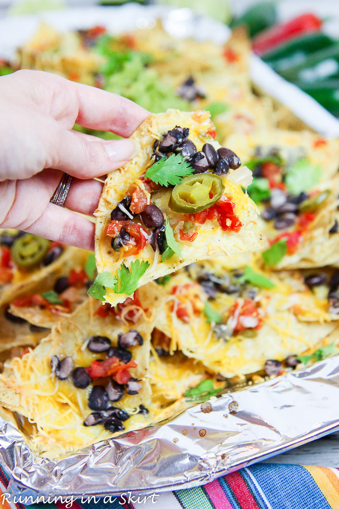 Hand with chip holding Vegetarian Nachos recipe