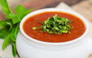 Easy Crock Pot Tomato Basil Soup in a white bowl with basil garnish on top.