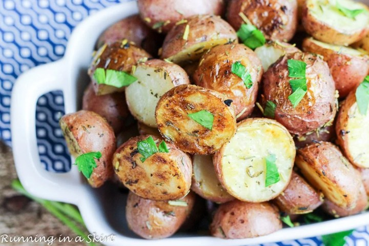 Herb and Garlic Roasted Baby Red Potatoes in a white baking dish.