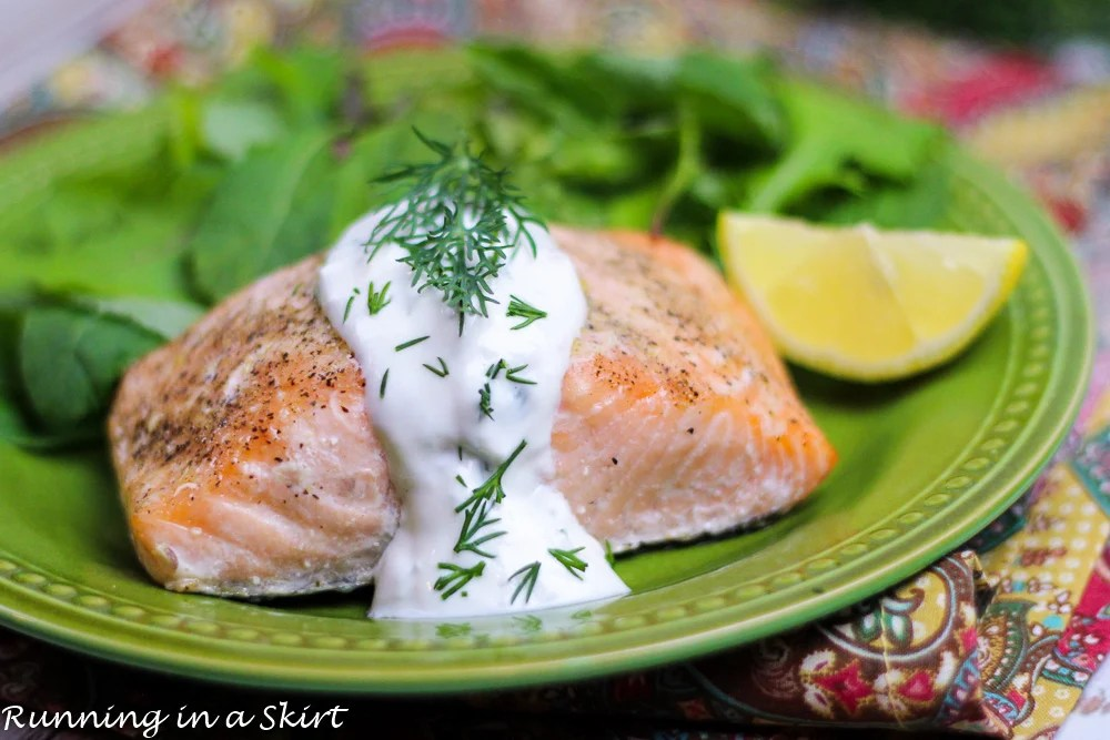 Baked Lemon Salmon with Creamy Dill Sauce on a green plate.
