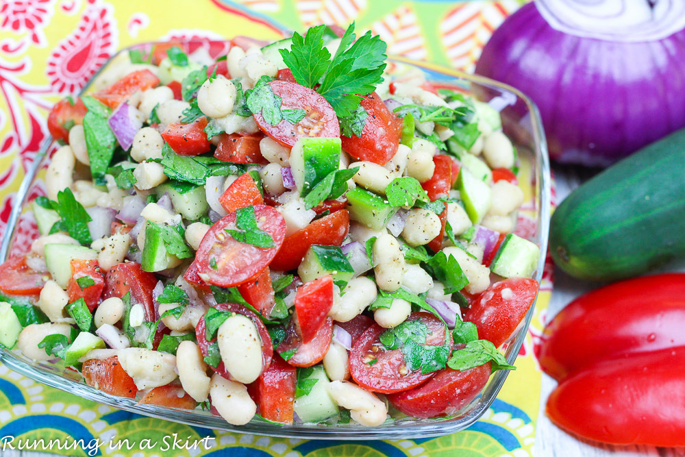 Vegan Bean Salad with fresh herbs, cucumber and tomato in a glass bowl.