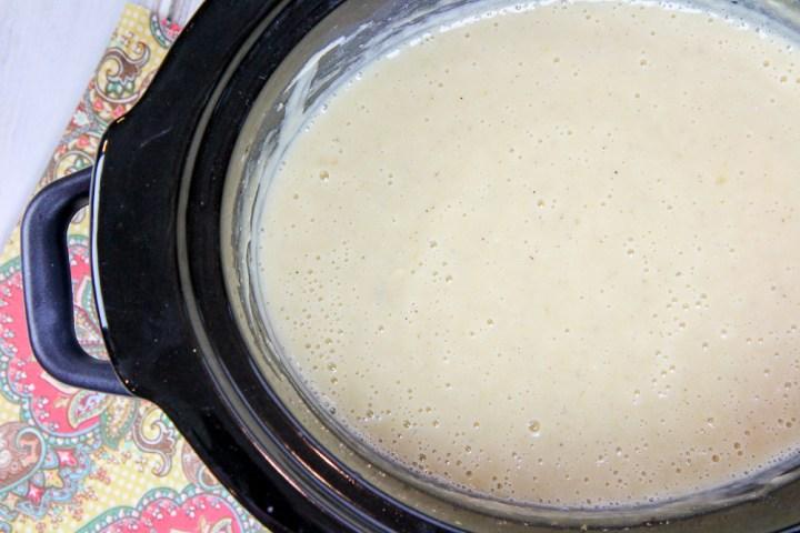 Crock pot with vegetarian potato soup cooking.
