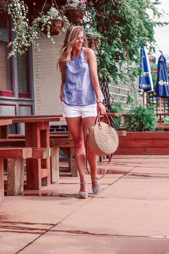 Prepare for Your First Spray Tan | Blonde, tan girl wears a chambray linen tank with white shorts, a round straw bag, and cork heeled sandals.