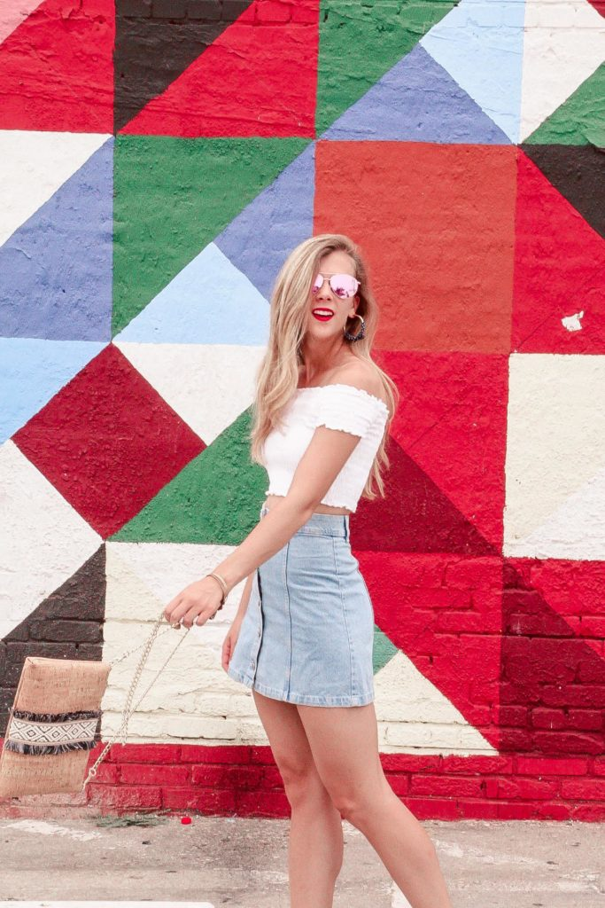 Murals of Dallas | Blonde Girl stands in front of geo print mural wearing white crop top and denim mini skirt