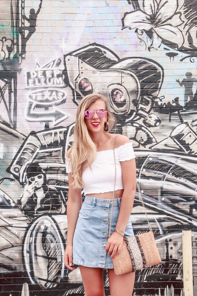 Murals of Dallas | Blonde Girls stands in front of robot mural wearing white crop top and denim mini skirt