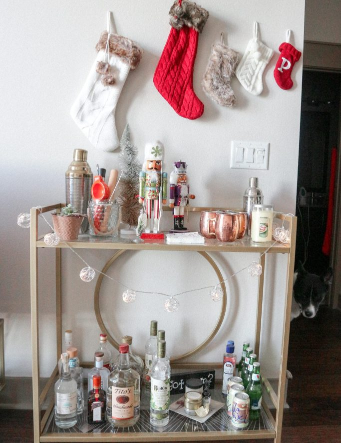 Christmas tree with dog in front shared in post, How to decorate an apartment for Christmas featured by top us fashion and lifestyle blogger, Running in Heels: Bar cart with stockings hung and holiday decor