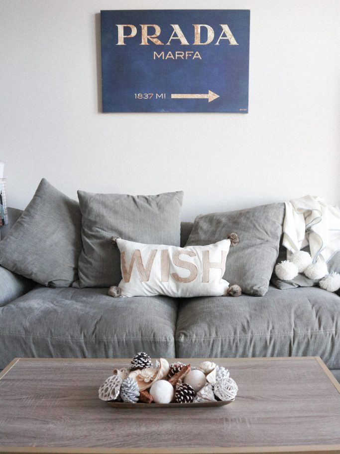 How to decorate an apartment for Christmas featured by top us fashion and lifestyle blogger, Running in Heels: Prada Marfa sign hung above gray couch