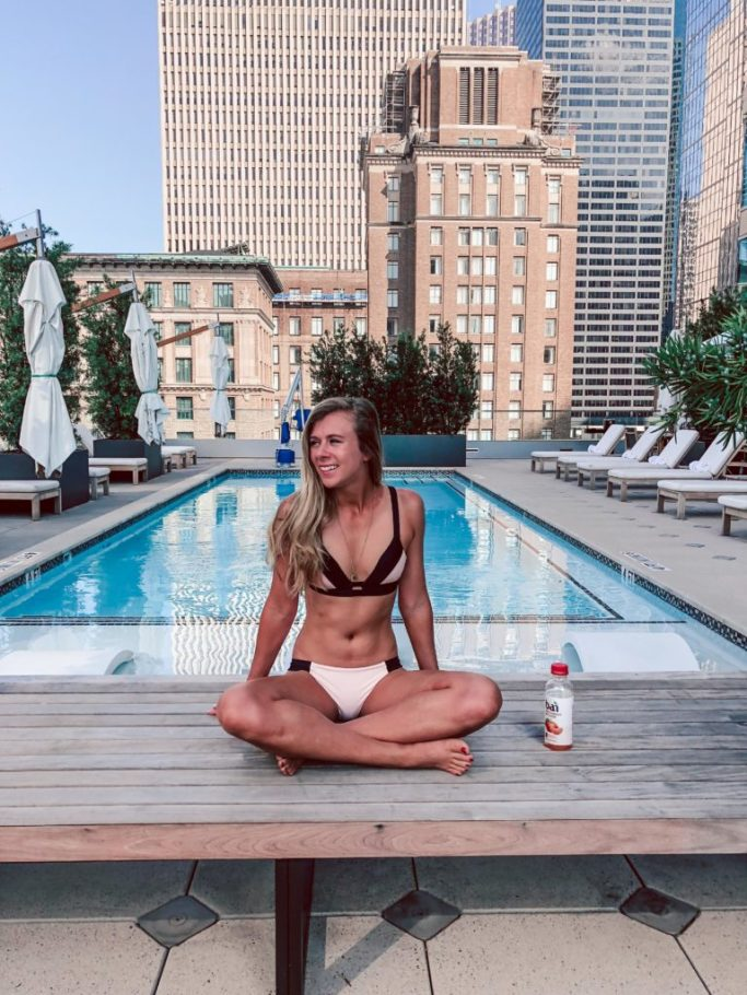 Where to stay in Houston: Hotel Alessandra | Dallas blogger, Running in Heels sits poolside wearing a pink and black bikini from Adore me with Bai juice next to her.