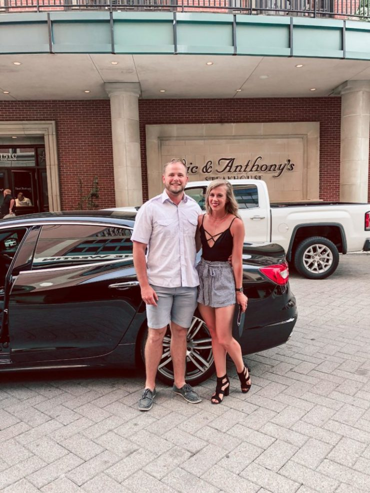 Getting Concert Ready with Palm Beach Tan: Blonde Dallas Blogger, Running in Heels stands with boyfriend in front of a Maserati at Vic & Anthony's Steakhouse in Houston. She wears Versa Pro Spray tan, black strappy bodysuit from Express, Gingham paper bag shorts, and black strappy heels, with a black Kate Spade Clutch, he wears a short sleeve button down, shorts, and boat shoes.