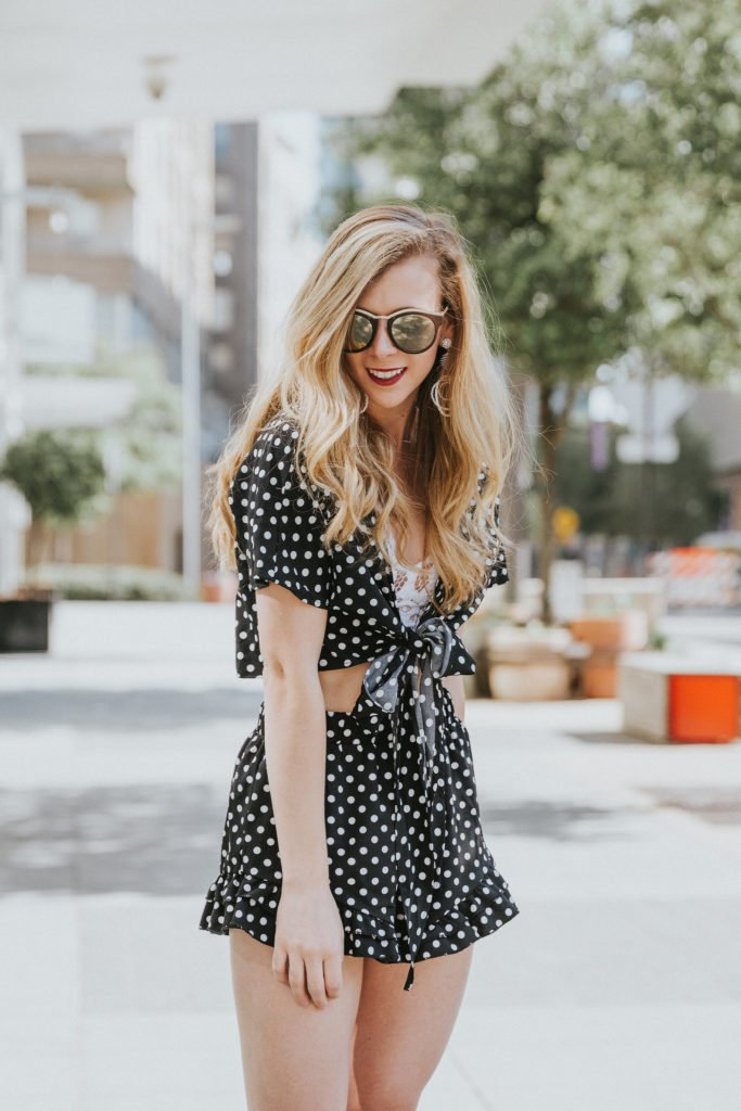 Two-pieces polka dot set on blonde fashion blogger in Victory Park, Dallas. This summer outfit is styled with a lace bralette, mirrored sunglasses, and black and straw wedges.