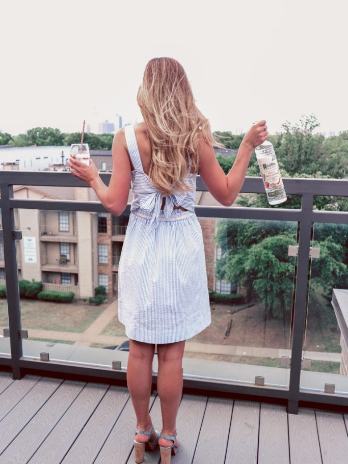 Ketel One Botanical   Rooftop views, Peach and orange blossom with soda. Blonde holding drink and bottle looking out to the city wearing a seersucker blue and white striped dress with a bow in the back.