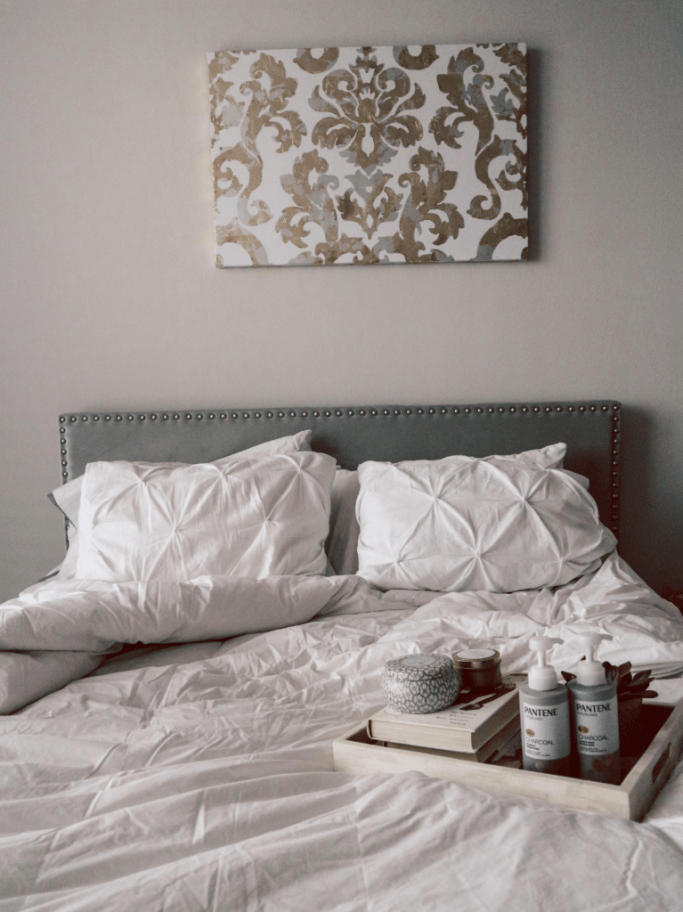 Pantene Charcoal Collection on white bed with gray headboard with gold and silver foil canvas