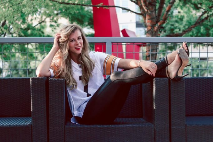 How To Dress Up Your Game Day Style   blonde girl sitting in a chair wearing a Steelers jersey, spanx leggings, and heels
