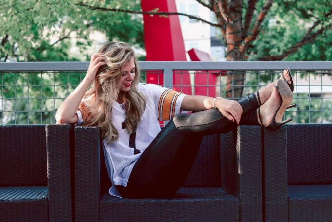 How To Dress Up Your Game Day Style | blonde girl sitting in a chair wearing a Steelers jersey, spanx leggings, and heels