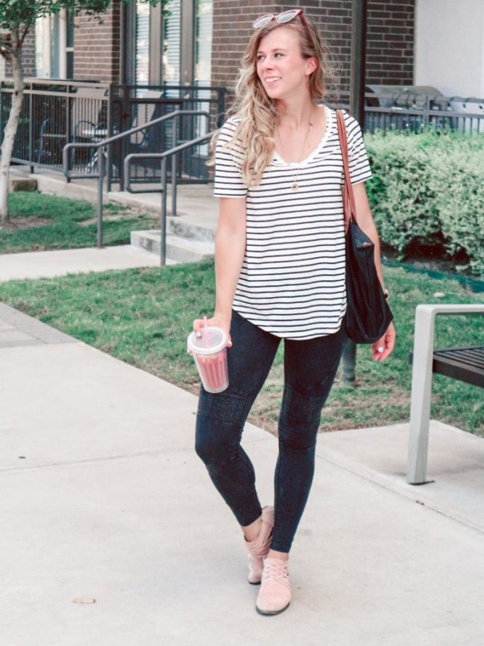Girl wearing casual outfit with a striped t-shirt, black leggings, sunglasses, with black bag, carrying Stok iced coffee