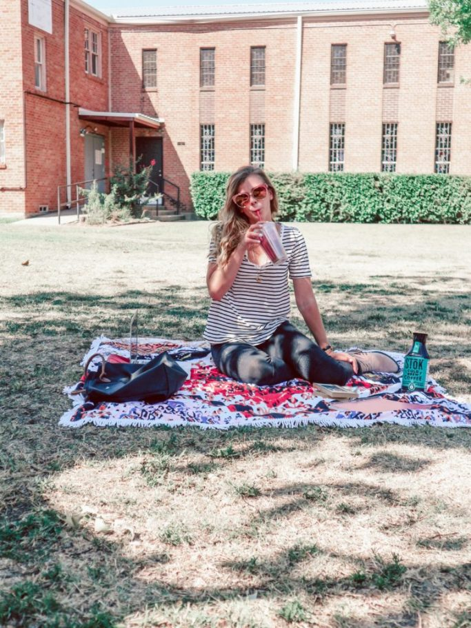 Girl wearing casual outfit with a striped t-shirt, black leggings, sunglasses, while sitting on blanket on lawn with computer, books, and Stok iced coffee