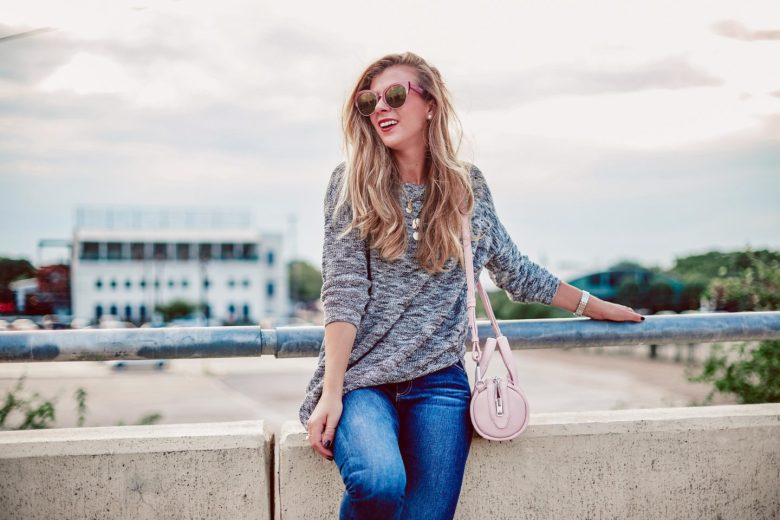 2018 Fall Trends I'm NOT Wearing | blonde sits on bridge in Dallas wearing a grey 3/4 sleeve sweater from Express, blue jeans by DL1961, and DIFF sunglasses. She carries her pink Alexander Wang baby Rockie bag and gold coin baublebar necklace.