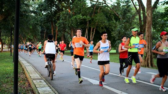 A cyclist rides head-on into the mass of runners