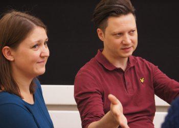Frau und Mann im Gespräch mit Zuhörenden