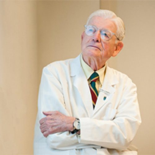 Paul Russell MD older physician with glasses and white coat