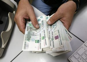An employee counts Russian ruble banknotes at a private company's office in Krasnoyarsk