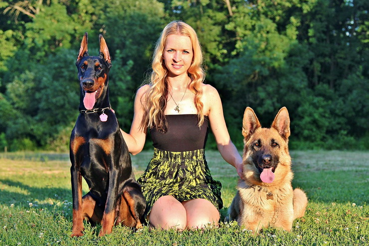 young woman with german shepherd and doberman