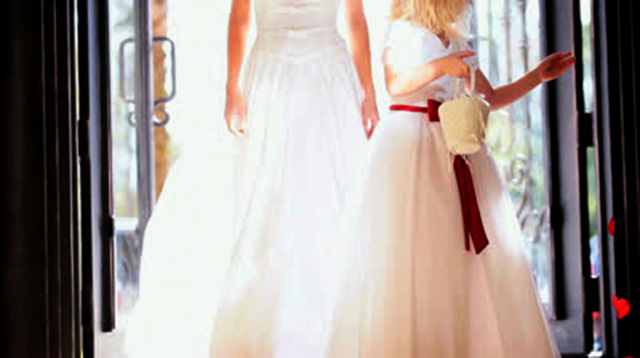 stock-footage-pretty-blonde-flower-girl-scattering-red-rose-petals-in-front-of-walking-bride-sun-lens-flare